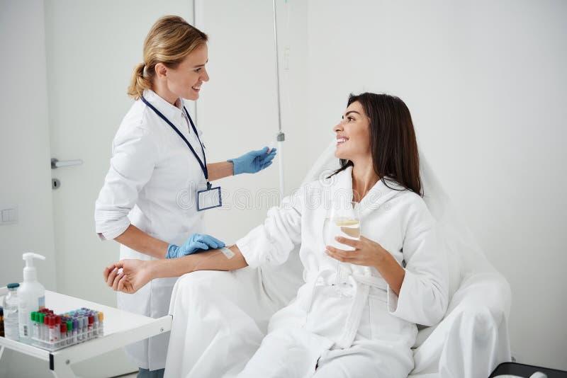 Doktor, der intravenösen Tropfenfänger beim Betrachten junger Dame mit Lächeln reguliert lizenzfreie stockfotografie