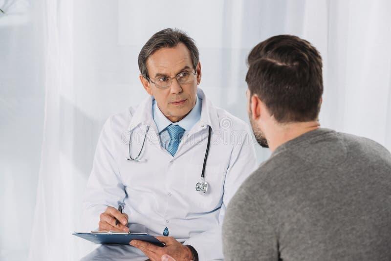 Doktor, der Klemmbrett anhält lizenzfreie stockfotos