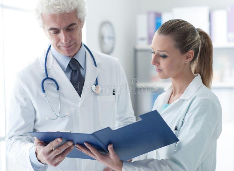 Doktor, der Krankenblätter überprüft lizenzfreies stockbild