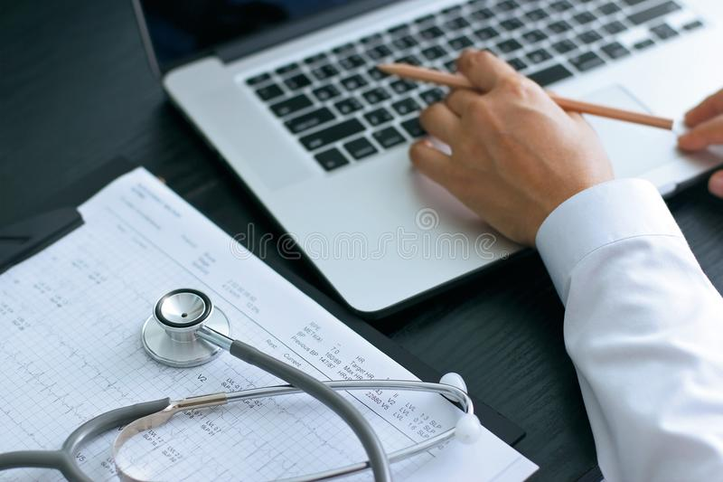 Doktor, der Laptop verwenden und Stethoskop auf Gesundheitswesen berichten stockfotografie