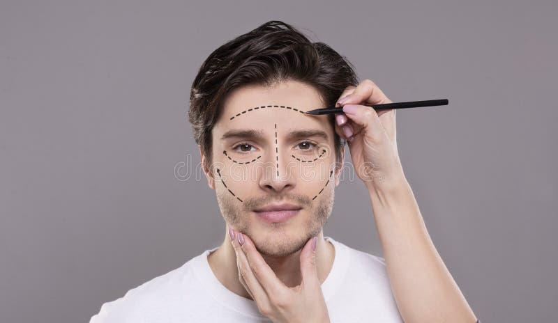 Doktor, der männliches Gesicht mit Korrekturlinien berührt stockfotos