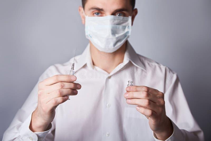 Doktor in der Maske mit einer Injektionsspritze auf dem blauen Hintergrund lizenzfreie stockbilder