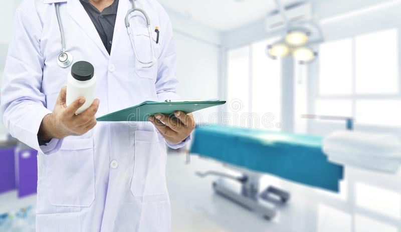 Doktor, der Medizinflasche im Operationsraum h?lt lizenzfreies stockfoto