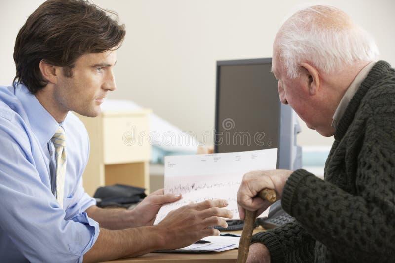 Doktor, der mit älterem männlichem Patienten spricht lizenzfreie stockfotografie