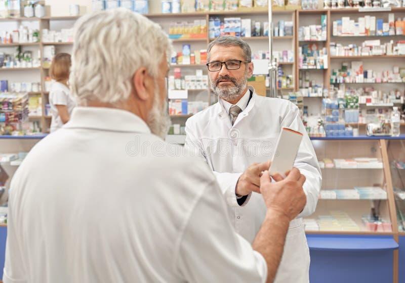 Doktor, der mit älterem Mann im Drugstore spricht lizenzfreie stockbilder