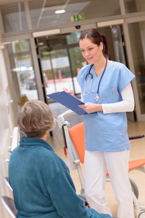 Doktor, der mit älterem Patienten im Krankenhaus spricht stockbild