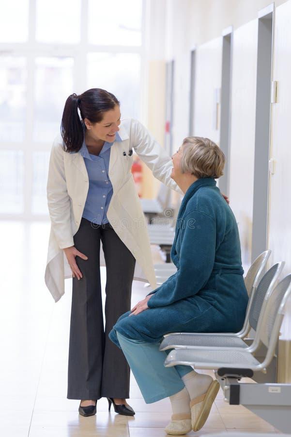 Doktor, der mit älterem Patienten lächelt lizenzfreie stockfotos