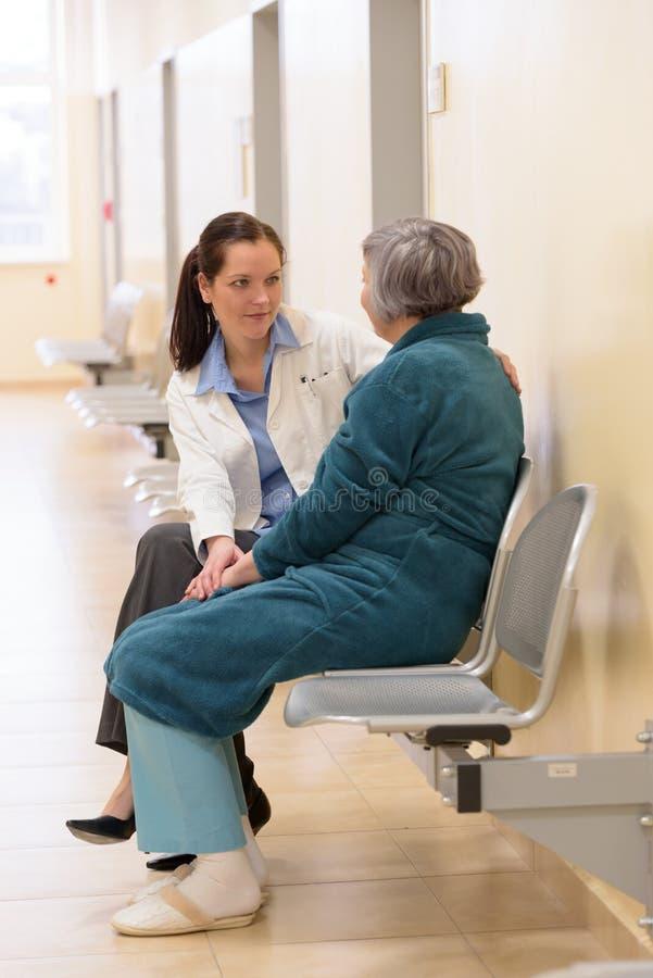 Doktor, der mit älterem Patienten sitzt stockfoto