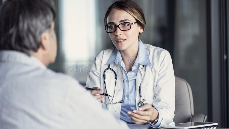 Doktor, der mit dem Patienten spricht lizenzfreies stockfoto