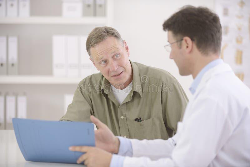 Doktor, der mit Patienten spricht stockbild