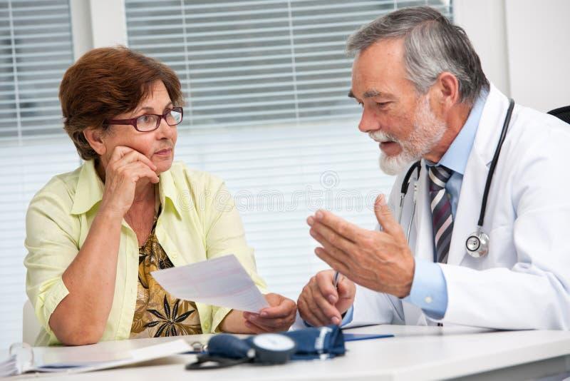 Doktor, der mit seinem weiblichen Patienten spricht stockbilder