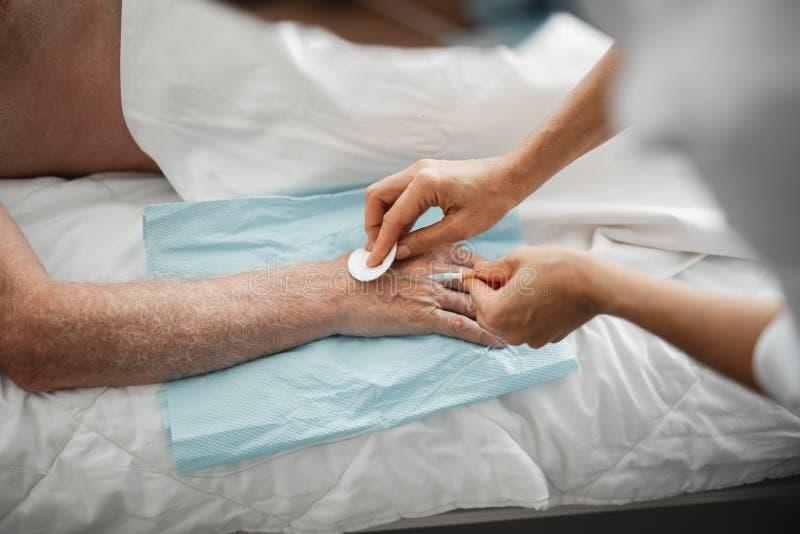 Doktor, der Nadel für IV Infusion auf Arm des alten Mannes befestigt lizenzfreies stockfoto