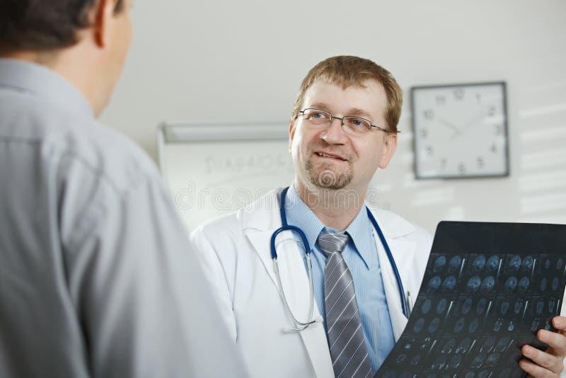 Doktor, der Patienten erklärt stockbild
