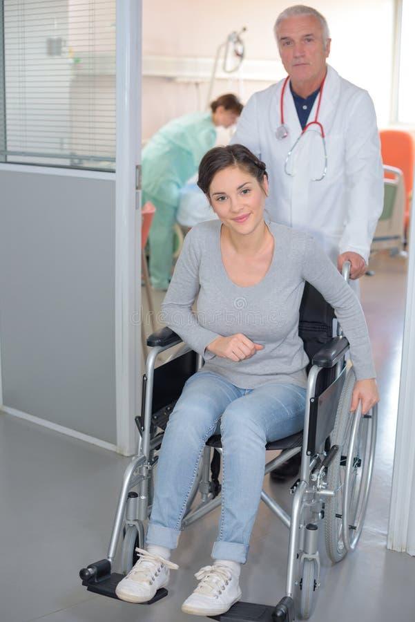 Doktor, der Patienten im Rollstuhl drückt lizenzfreie stockbilder