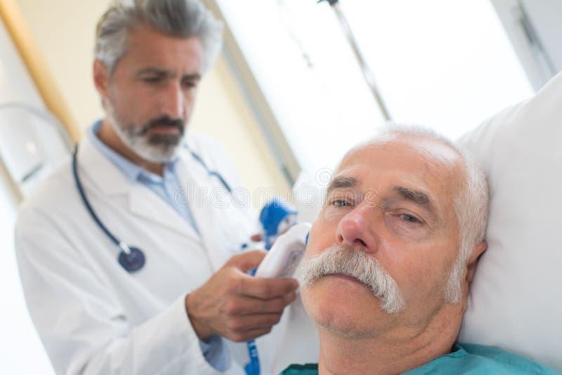 Doktor, der Patientenohr mit medizinischer Ausrüstung überprüft stockfotos