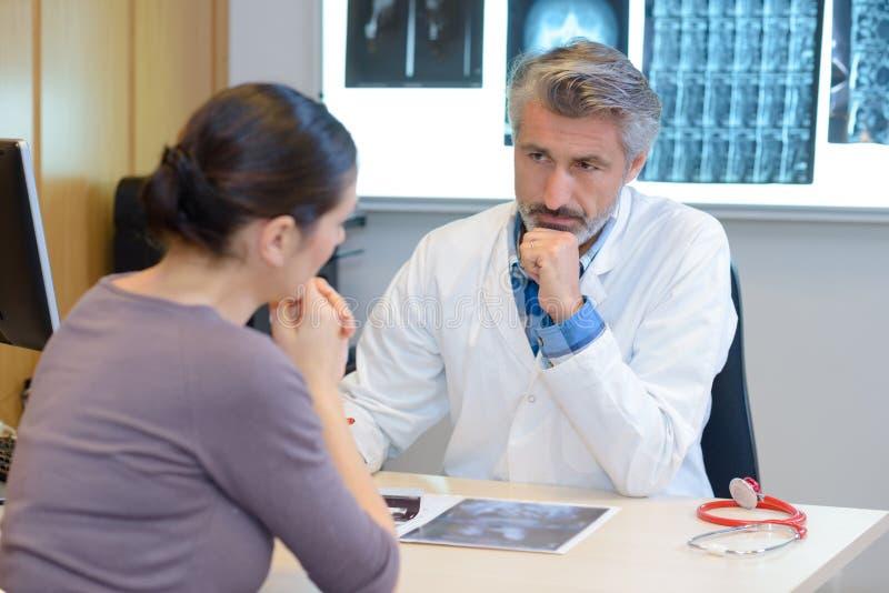 Doktor, der Patientinnengesundheit überprüft lizenzfreie stockbilder