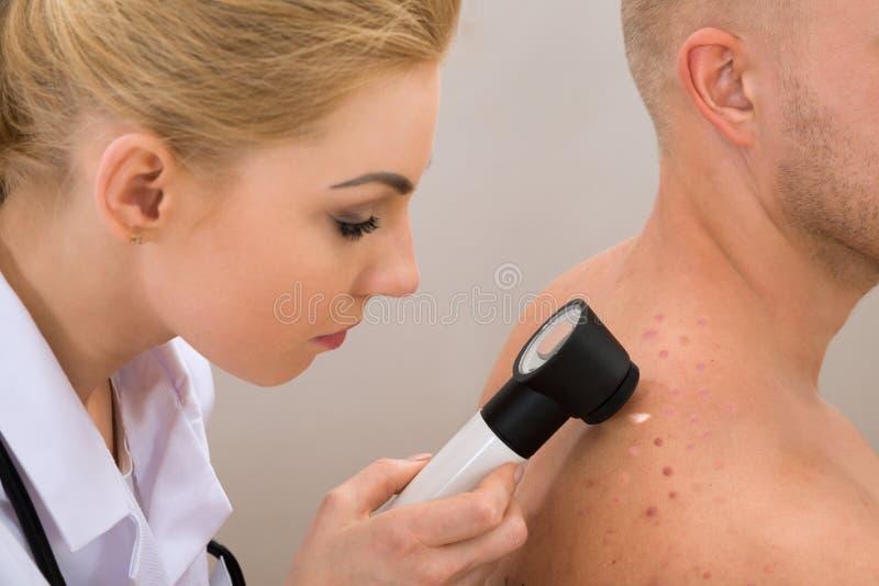 Doktor, der pigmentierte Haut überprüft lizenzfreie stockfotos