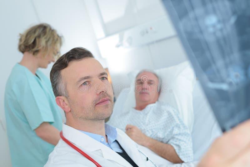 Doktor, der Röntgenstrahlpatienten im Hintergrund betrachtet stockfoto