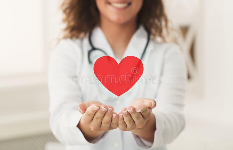Doktor, der rotes Herz in schalenförmigen Händen hält lizenzfreies stockfoto