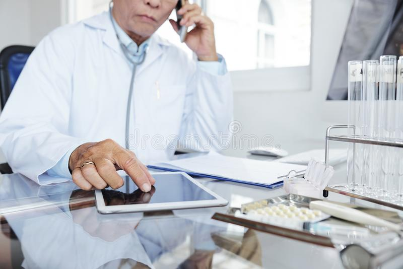Doktor, der an seinem Schreibtisch arbeitet lizenzfreies stockbild