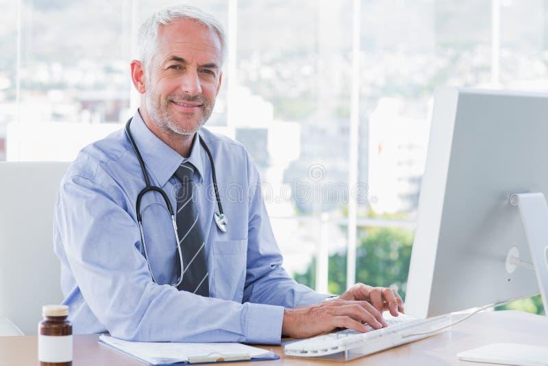 Doktor, der seinen Computer schreibt und verwendet lizenzfreies stockbild