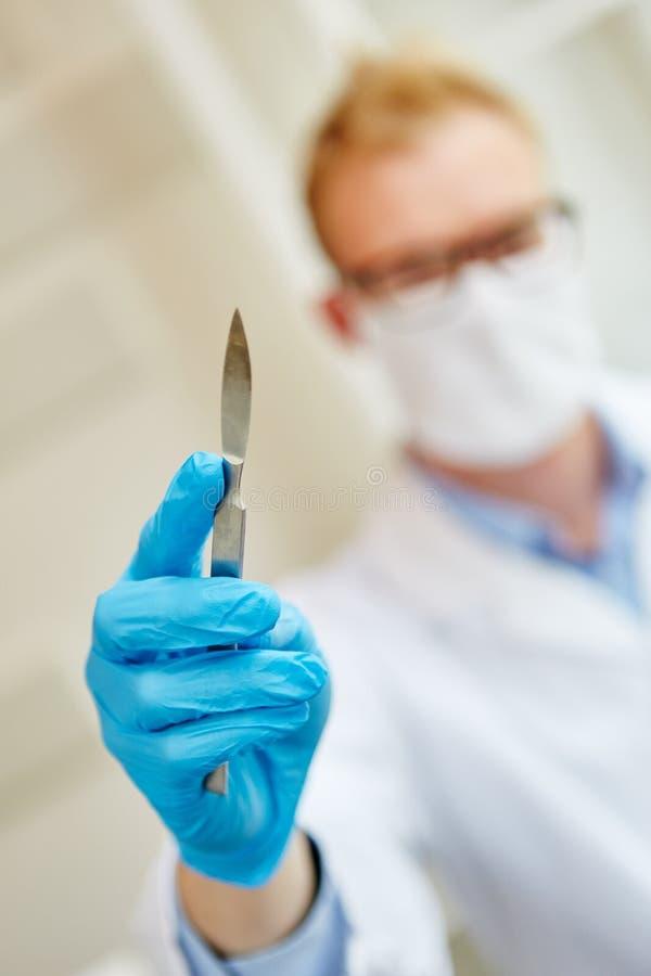 Doktor, der Skalpell hält lizenzfreies stockbild