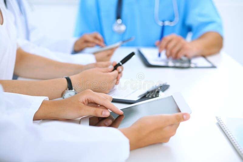 Doktor, der Tablet-Computer bei der medizinischen Sitzung, Nahaufnahme verwendet Gruppe Kollegen am Hintergrund lizenzfreie stockfotos
