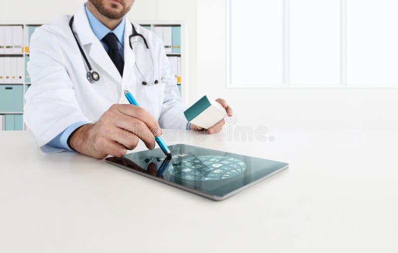 Doktor, der Tablette auf Schreibtisch verwendet, schreibt Medizin vor lizenzfreies stockbild