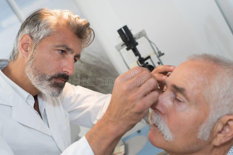 Doktor, der Tropfen in Senior setzt, bemannt Augen lizenzfreies stockbild