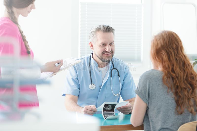 Doktor, der Ultraschallbild erklärt lizenzfreies stockbild