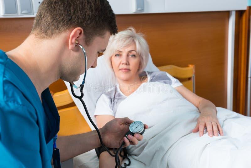 Doktor in der Uniform mit phonendoscope auf seinem Hals misst Th stockfoto
