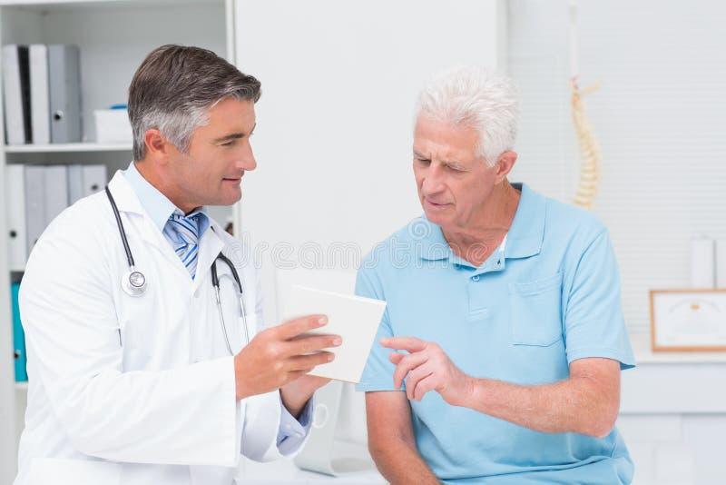 Doktor, der Verordnung älterem Patienten erklärt lizenzfreies stockbild