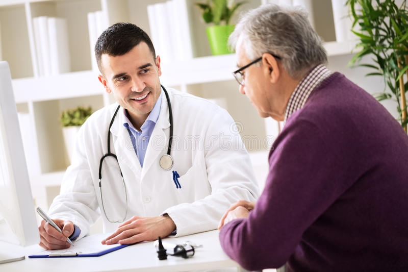 Doktor, der Verordnung älterem Patienten erklärt stockbilder