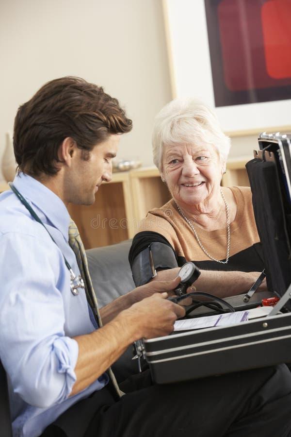 Doktor, der zu Hause Blutdruck der älteren Frau nimmt stockfoto