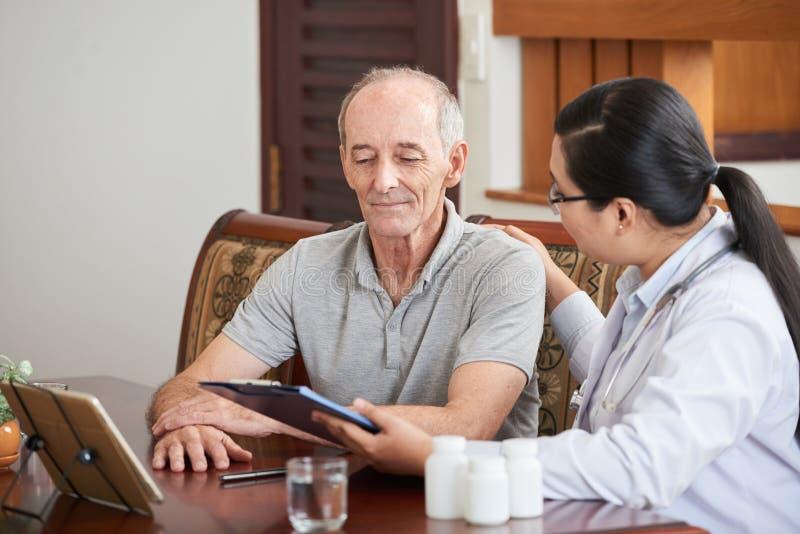 Doktor, der zu Hause mit Patienten spricht stockfotos