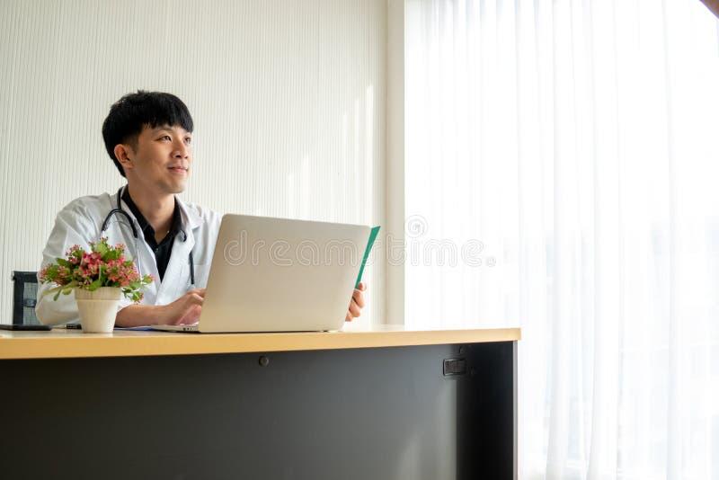 Doktor des jungen Mannes liest die Patientenakte und Fühlung, die in seinem Denken auf seinem Arbeitsschreibtisch überzeugt sind lizenzfreies stockbild