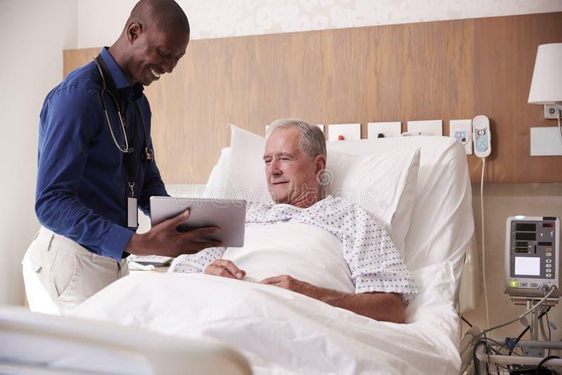 Doktor With Digital Tablet som besöker och talar med den höga manliga patienten i sjukhussäng royaltyfria foton