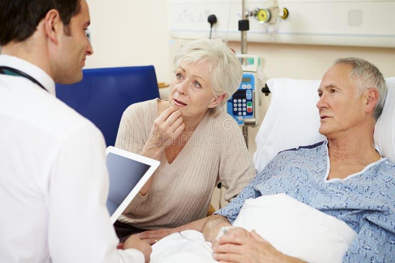 Doktor With Digital Tablet som talar till par vid sjukhussäng royaltyfria foton