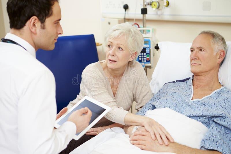 Doktor With Digital Tablet som talar till par vid sjukhussäng arkivfoto