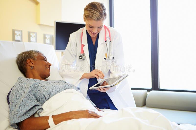 Doktor With Digital Tablet talar till kvinnan i sjukhussäng royaltyfria bilder