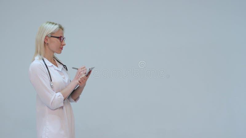 Doktor in einem weißen Hausmantel und im Stethoskoplächeln, Aufzeichnungen die Instrumente lizenzfreies stockfoto
