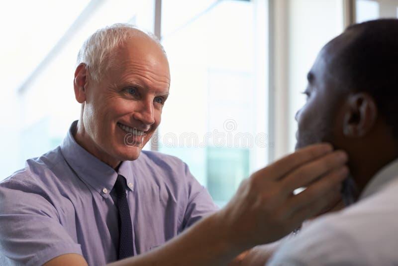 Doktor Examining Male Patient i regeringsställning arkivfoto