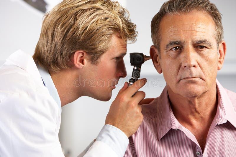 Doktor Examining Male Patients Ears stockbild