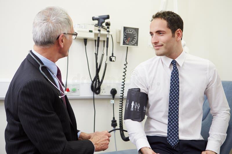 Doktor Examining Senior Patient i sjukhus royaltyfria foton