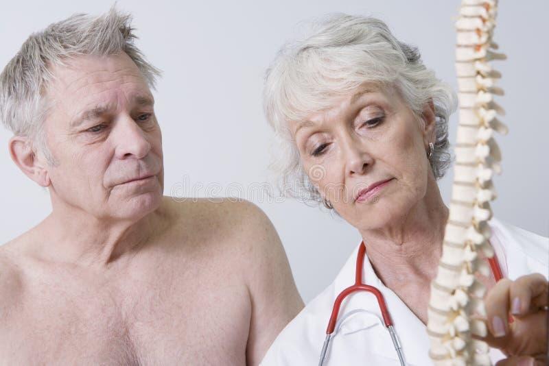 Doktor Explaining The Problems om ryggmärg till patienten arkivfoto