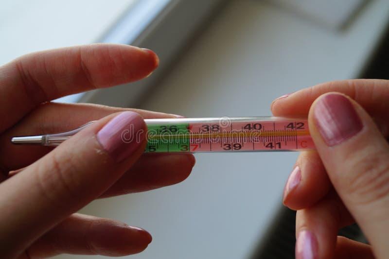 Doktor för hand- för flicka` som s rymmer en kvicksilvertermometer royaltyfri fotografi