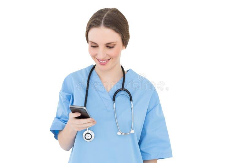Doktor för ung kvinna som ser hennes smartphone fotografering för bildbyråer