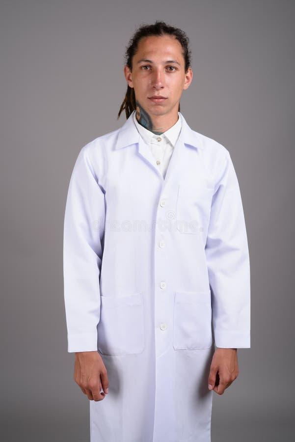 Doktor f?r ung man med dreadlocks mot gr? bakgrund fotografering för bildbyråer