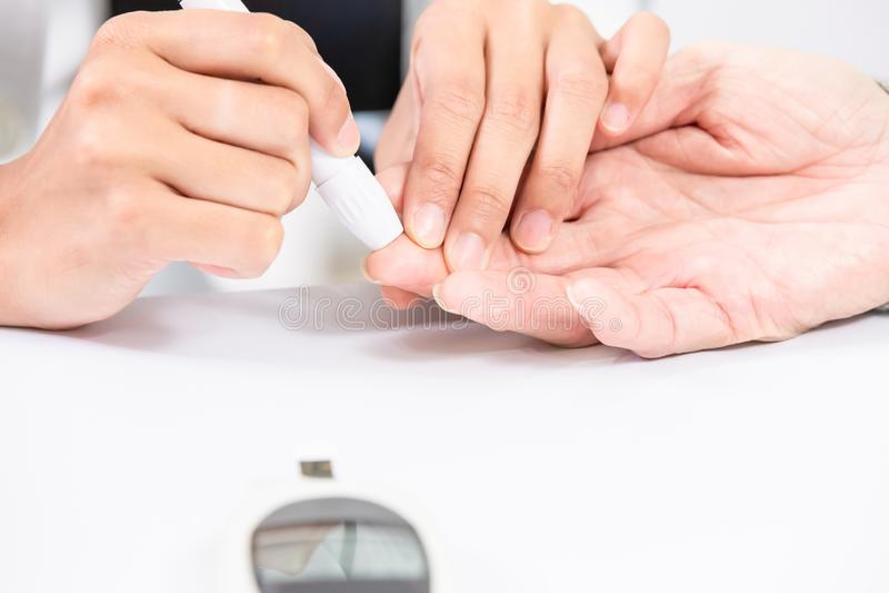 Doktor führen Blutzuckertest durch lizenzfreies stockbild