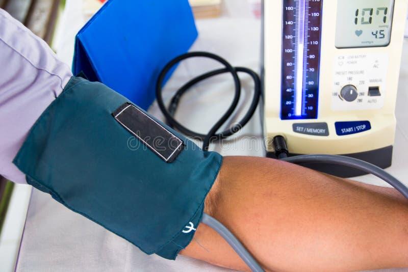 Doktor forscht den Blutdruck nach stockbild
